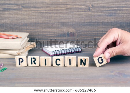 pricing. Wooden letters on dark background #685129486