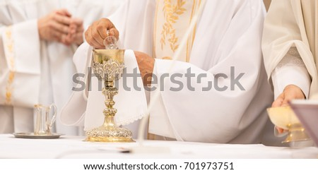 Priest during a wedding ceremony/nuptial mass (shallow DOF; color toned image)