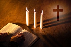 Priest hands on bible. Burning candles next to Christian cross. Cross symbolizes Catholicism or Orthodox. Attributes of Christianity on a wooden table. Catholic prays to God. Orthodox studying bible