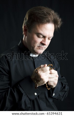 Priest holding his rosary and praying.  Black background and dramatic lighting.