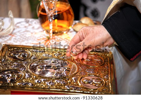 priest holding wedding rings on top of bible