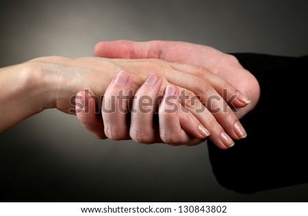 Priest holding woman hand, on black background