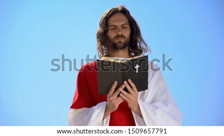 Priest in robe reading Holy Bible, closing eyes to pray, Christian theology Stock photo ©