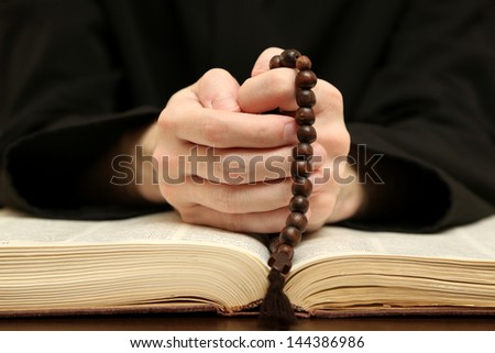 Priest reading from the holy bible close up