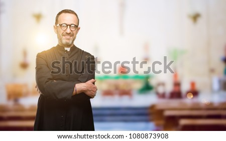Priest religion man with crossed arms confident and happy with a big natural smile laughing at church Stock fotó ©
