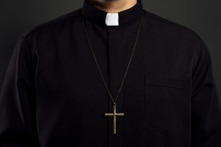 Priest with cross on black background, closeup