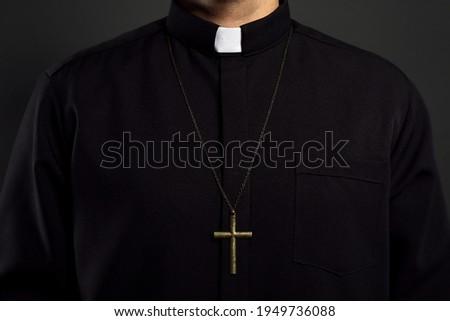 Priest with cross on black background, closeup Stock fotó ©