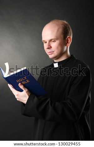Priest with Holly Bible on black background