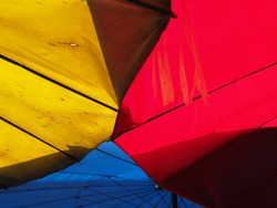 Primary colors background blue-red-yellow with outdoor umbrellas at a morning market in Thailand. Concept of primary colors.