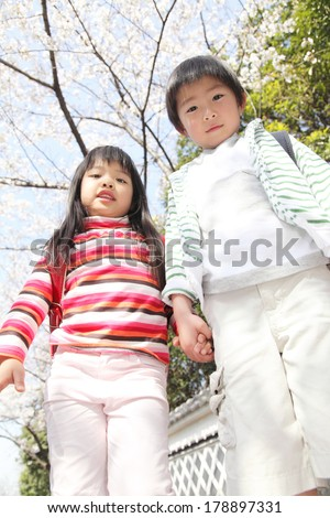 Primary Japanese boy and Japanese girl who are standing under the cherry tree