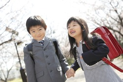 Primary Japanese boy and Japanese girl who walks on the path lined with cherry blossom trees