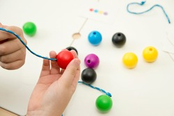 Primary Lacing Beads - Educational Toy With Wooden Balls. Colourful rainbow wooden lacing toy for toddlers. Threading toy for fine motor skills development. Boy holding ball with lace