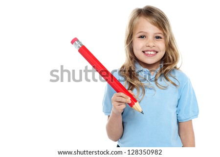 Primary school child posing with a big red pencil in hand,flashing a toothy smile.