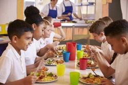 Primary school kids eating at a table in school cafeteria
