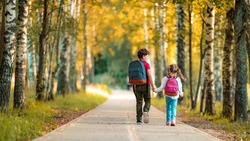 Primary school pupil. boy and girl with backpacks walking down street. Happy children happy to go back to school. beginning school year. Children in full growth, with joy went to school. rear view