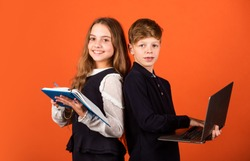 Primary school pupils. Little pupils hold book and laptop brown background. Small pupils study at school. Smart pupils or schoolchildren. E-learning and online education. New technology.
