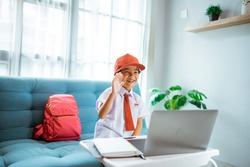 primary school student with uniform waving to her teacher and friend during online class session