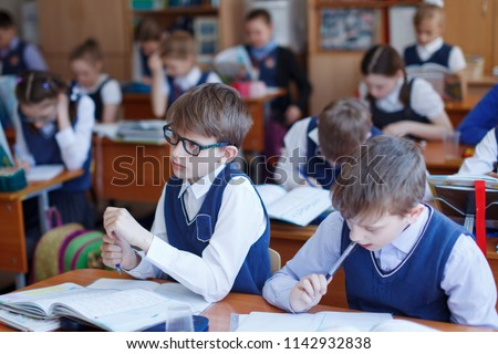 Primary school students think and perform tasks in the classroom. The concept of primary education, training and human resources.