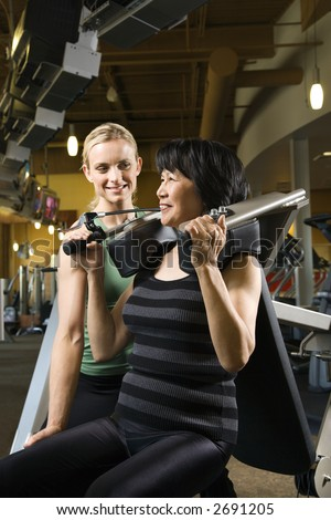 stock photo : Prime adult Caucasian female trainer helping Asian mature ...