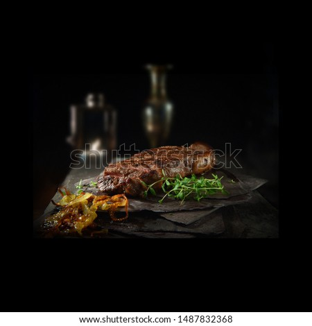 Prime fillet beef steak, grilled to perfection with fried onions and thyme garnish. Shot against a dark background with accommodation for copy space. The perfect image for your menu cover art.