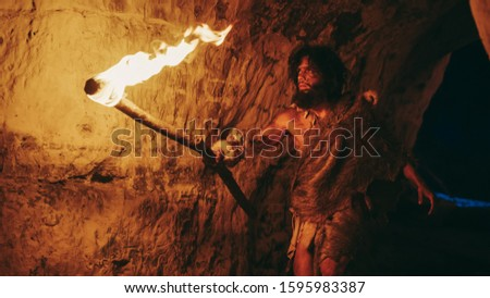 Primeval Caveman Wearing Animal Skin Exploring Cave At Night, Holding Torch with Fire Looking at Drawings on the Walls at Night. Neanderthal Searching Safe Place to Spend the Night