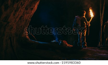 Primeval Caveman Wearing Animal Skin Stands in a Cave At Night, Holding Torch with Fire Looking Out of The Cave at Night. Back View