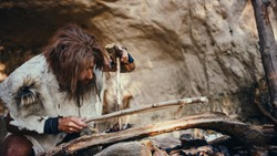 Primeval Caveman Wearing Animal Skin Trying to make a Fire with Bow Drill Method. Neanderthal Kindle First Man-Made fire in the Human Civilization History. Making Fire for Cooking.