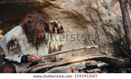 Primeval Caveman Wearing Animal Skin Trying to make a Fire with Bow Drill Method. Neanderthal Kindle First Man-Made fire in the Human Civilization History. Making Fire for Cooking. Stock photo ©