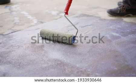 Priming the concrete floor with a roller. Professional floor primer. Leveling concrete floors. Floor repair using a primer. Stockfoto ©