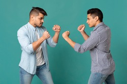 Primitive Instincts And Male Behavior. Strong Arab Guys Posing With Clenched Fists Preparing For Fight On Turquoise Studio Background