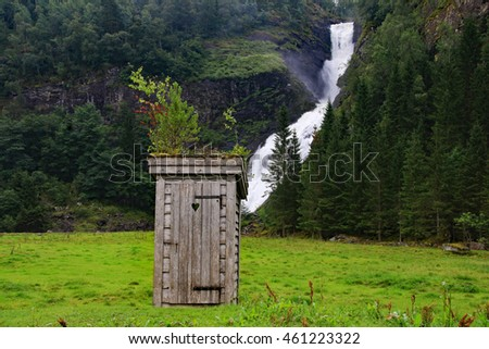 Primitive outdoor privy in front of a foaming waterfall