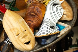 Primitive wooden masks, in the foreground a smiling face close-up, selective fokus.