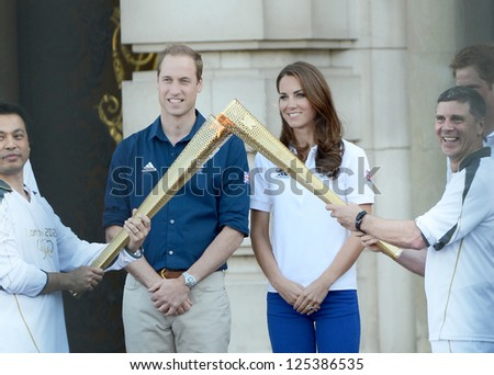 Prince William and Catherine, Duchess of Cambridge welcome the olympic torch to Buckingham Palace, London, UK. July 26, 2012.