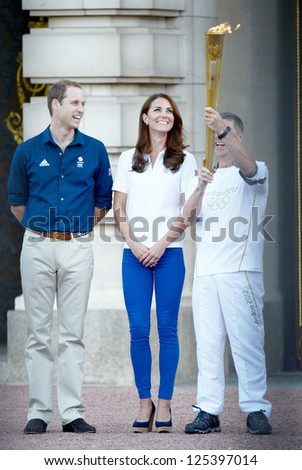 Prince William and Catherine, Duchess of Cambridge welcome the olympic torch to Buckingham Palace, London, UK. July 26, 2012. - stock photo
