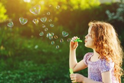 Princess girl blowing soap bubbles with heart shaped, happy childhood concept.
