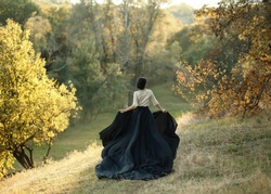 Princess in a vintage dress. Walk along landscape autumn hills, park at sunset. A long train of black skirt fluttered on the run. Photo of a young witch with a back without a face. Art Photography