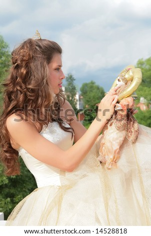 princess in white-golden gown plays with loved doll on background cloudy sky