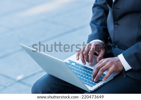 print hands. African man businessman holding a laptop on his knees and looking at the laptop while sitting outdoors in formalwear and hands typing on the keyboard
