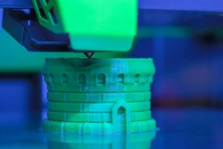 Print head of 3D printer machine printing green plastic model at modern scifi technology exhibition, factory: closeup. 3D printing, additive technology, futuristic concept