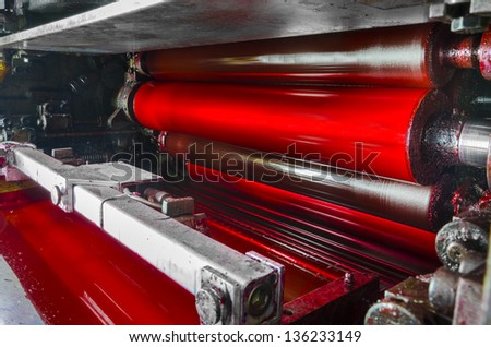 print machine printing press rollers, red magenda color drum, dramatic light