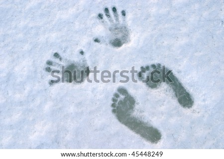 print of human foots and palms on blue ice - stock photo