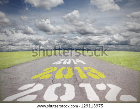 Print of the timeline for Year 2012, 2013 and 2014 on an asphalt road vanishing into the horizon of mountain range on a blue cloudy day, for the concept of yearly deadline.