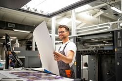 Print shop worker checking quality of imprint and controlling printing process.