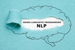Printed acronym NLP Neuro Linguistic Programming appearing behind torn blue paper in human brain drawing.