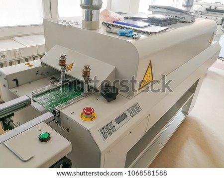 Printed circuit board after full assembly moves to reflow oven machine for heating up soldering paste