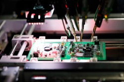 Printed circuit board assembly during a flying probe In-circuit test on flying probe tester system. Selective focus.