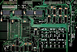 Printed Circuit board from a computer in black with green lines depicting connections.