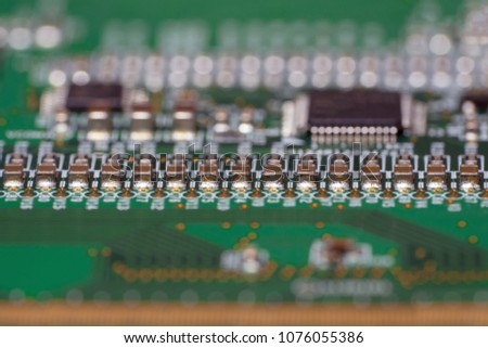 Printed circuit board with SMD capacitors close-up. Macro photography of a fragment of the decoder panel tft LCD monitor with installed electronic components. #1076055386