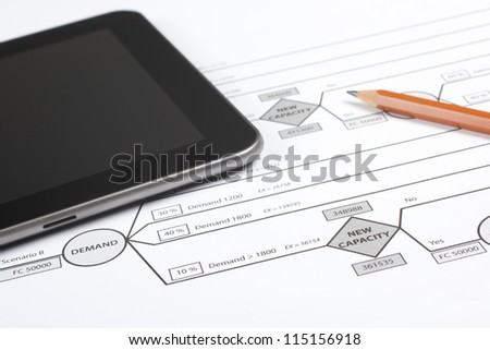 Printed decision tree (new factory capacity expansion), digital tablet and pencil. Workplace of manager making decision about strategy.