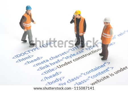 Printed HTML code of website (internet page) under construction. Construction worker figurines working on code.